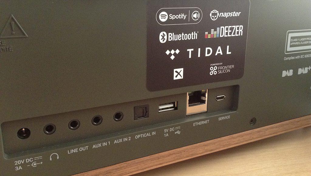 Détail des connectiques de la Como Audio Musica de gauche à droite : entrée alimentation, sortie casque, sortie analogique mini-jack, deux sorties analogique mini-jack, une entrée numérique optique, une entrée USB, une entrée Ethernet RJ45, une prise pour le service
