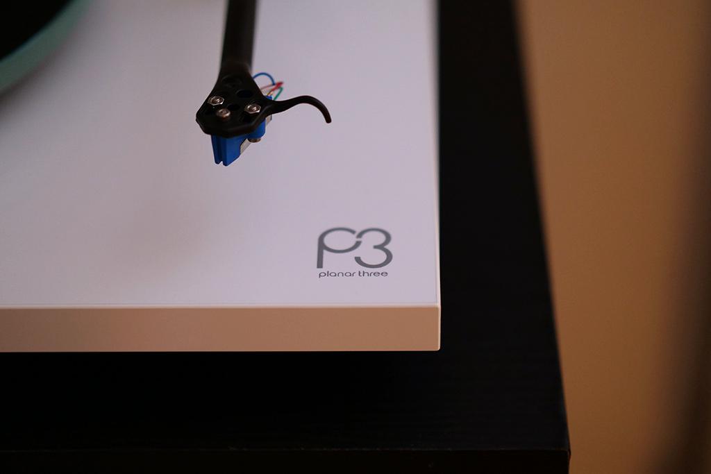 Détail du logo de la platine Rega Planar Three affiché sur le socle laqué blanc.