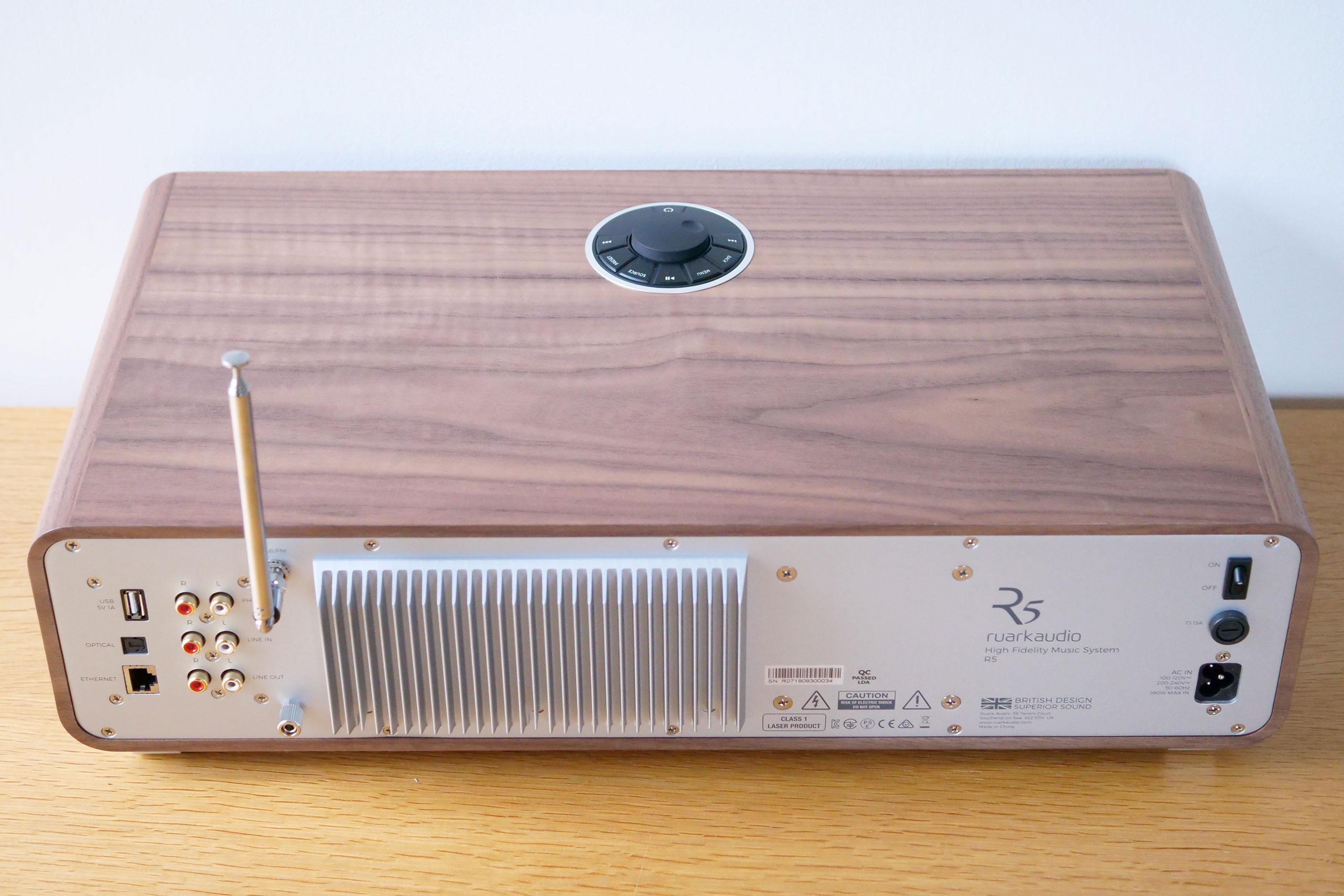 Sur la face arrière, les prises sont situées à gauche, le radiateur de l'amplificateur de classe AB interne au centre et le commutateur marche/arrête à droite.